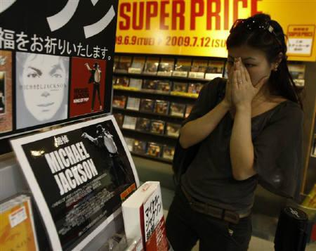 A Japanese fan reacts as she looks at commemorative stand for Michael Jackson at a music shop in Tokyo June 26, 2009. REUTERS/Kim Kyung-Hoon
