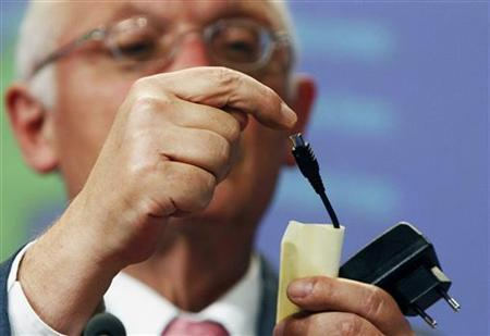 European Industry Commissioner Guenter Verheugen shows a mobile phone charger at a news conference in Brussels June 29, 2009. Top mobile telephone suppliers have agreed to back an EU-wide harmonisation of phone chargers, the European Commission said on Monday, hailing the pact as good news for consumers and the environment. REUTERS/Thierry Roge