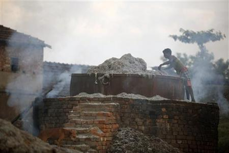 A labourer works on a burning oven to make fertilizer ingredients out of scrap leather at a roadside factory in Kolkata May 4, 2007. REUTERS/Parth Sanyal