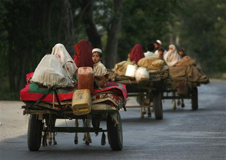 Families make their way to Buner district from Mardan by cart, about 220 km (137 miles) by road northwest of Islamabad July 1, 2009. REUTERS/Akhtar Soomro