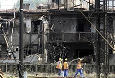 <p>Soccorritori a lavoro accanto a case bruciate a Viareggio. REUTERS /Stefano Rellandini (ITALY DISASTER)</p>