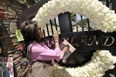 <p>Fã Jenny Tanner segura um livro de Michael Jackson do lado de fora do portão de Neverland na Califórnia. 01/07/2009. REUTERS/Phil Klein</p>