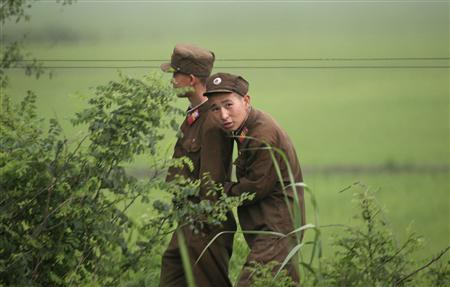 North Korean soldiers walk along the North Korean/ Chinese border near the North Korean town of Sinuiju, opposite the Chinese city of Dandong, July 2, 2009. REUTERS/Jacky Chen