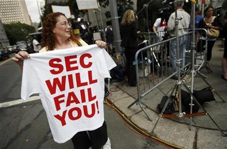 A woman holds up a T-shirt with a message referring to the Securities and Exchange Commission outside the United States Courthouse in lower Manhattan, June 29, 2009, during the sentencing hearing for convicted swindler Bernard Madoff. REUTERS/Shannon Stapleton
