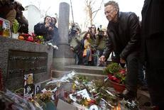 <p>Рэй Манзарек клавишник легендарной американской рок-группы The Doors (справа) кладет розу на могилу вокалиста группы Джима Моррисона на парижском кладбище Пэр Ляшез 8 декабря 2003 года. Календарь Рейтер знакомит с самыми значительными событиями в мире, произошедшими 3 июля, начиная с 1900 года. REUTERS/John Schults</p>