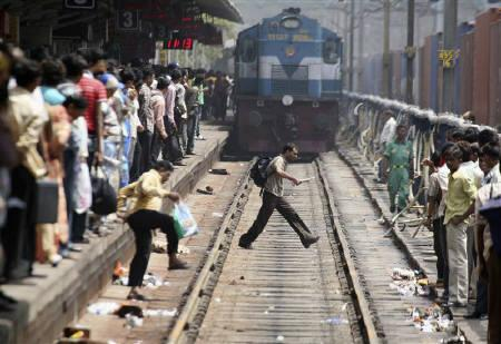 Passengers cross a railway track at a railway station in Ahmedabad July 3, 2009. REUTERS/Amit Dave