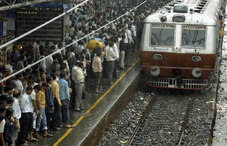 Commuters wait as a train approaches a railway station in Mumbai July 3, 2009.  REUTERS/Punit Paranjpe