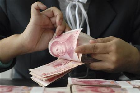An employee counts Renminbi banknotes at a branch of China Post Bank in Baokang, Hubei province April 10, 2008. REUTERS/Stringer