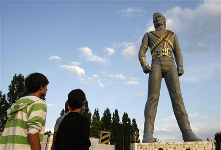 People stand in front of a 12-metre-high statue of late pop icon Michael Jackson in Regensdorf near Zurich July 3, 2009. REUTERS/Arnd Wiegmann
