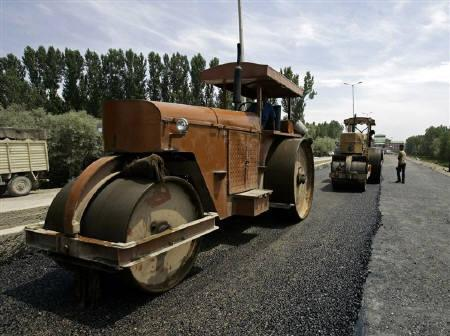 Workers use road rollers during the rebuilding process of a road in Srinagar July 2, 2009. REUTERS/Fayaz Kabli