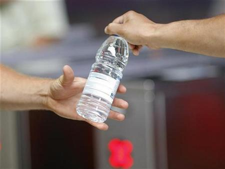 A man hands a bottle of water to another man in Sydney, February 6, 2009. REUTERS/Tim Wimborne