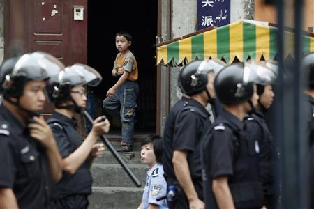 An ethnic Uighur boy stands at the door of his home as Chinese security forces secure the area in Urumqi in China's Xinjiang Autonomous Region July 10, 2009. REUTERS/Nir Elias