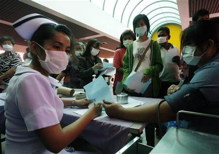 People wearing disposable masks attend a campaign promoting the use of face masks to prevent infection by the H1N1 flu virus, at a hospital in Nonthaburi province, on the outskirts of Bangkok, July 13, 2009. REUTERS/Chaiwat Subprasom