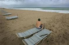 """<p>Турист смотрит на волны на пляже в городе Форт-Лодердейл перед тропическим ураганом """"Катрина"""". 25.08.2005. Деньги отдыхающих, чей отпуск был безнадежно испорчен плохой погодой, теперь могут возместить французские турагентства, которые предлагают новый вид страхования. REUTERS/Carlos Barria</p>"""