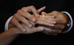 <p>Swiss groom Yann Deleurant puts a wedding ring on his bride Patrizia during their wedding ceremony in the traditional City Hall in Lucerne August 8, 2008. REUTERS/Michael Buholzer</p>