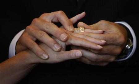Swiss groom Yann Deleurant puts a wedding ring on his bride Patrizia during their wedding ceremony in the traditional City Hall in Lucerne August 8, 2008. REUTERS/Michael Buholzer