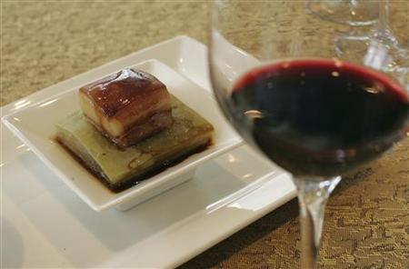 A dish of braised pork belly is pictured with a glass of Bin 389 Cabernet Shiraz 2005 Penfolds, from Australia in Hong Kong May 22, 2009. REUTERS/Aaron Tam