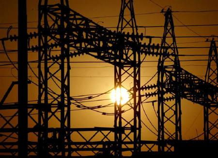 The sun sets behind electric pylons in Allahabad in this February 22, 2006 file photo. REUTERS/Jitendra Prakash/Files