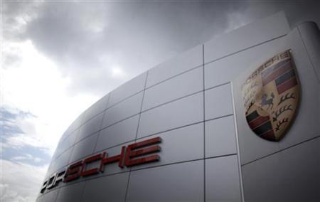 Dark clouds are seen over the logo of German car manufacturer Porsche outside a Porsche dealer in Frankfurt, June 22, 2009. REUTERS/Kai Pfaffenbach