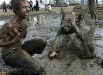 <p>Young people play in mud-water as they attend the 13th edition of the Woodstock Festival, organised by The Great Orchestra of Christmas, in Kostrzyn along Odra River, close to the Polish and German border, western Poland August 04, 2007. REUTERS/Kacper Pempel</p>