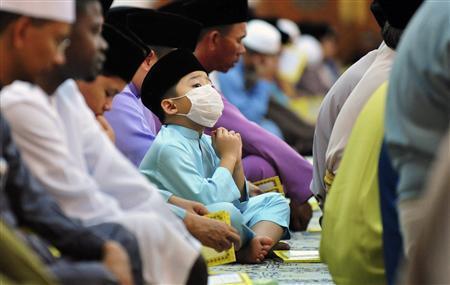 A Muslim boy wearing a face mask recites a thanksgiving prayer for the 63rd birthday anniversary of Brunei's Sultan Hassanal Bolkiah in Bandar Seri Begawan July 14, 2009. REUTERS/Ahim Rani