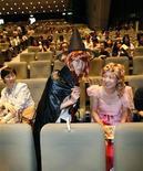 """<p>Поклонники Гарри Поттера, одетые в костюмы персонажей фильа, занимают места в кинозале на премьере картины """"Гарри Поттер и принц-полукровка"""" в Токио 6 июля 2009 года. Новый фильм о приключениях подростка-волшебника Гарри Поттера стартовал в мировом прокате с новым рекордом, принеся создателям в первый день уже $104 миллиона, сообщила кинокомпания Warner Bros. REUTERS/Kim Kyung-Hoon</p>"""
