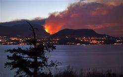 <p>A forest fire burns on the edge of Kelowna, British Columbia, northeast of Vancouver at dawn July 19, 2009. A fast-growing wild fire has forced thousands of residents of a western Canadian community to flee their homes, officials said on Sunday. The blaze erupted Saturday afternoon, quickly consuming at least 300 hectares and destroying at least nine houses in a residential area. REUTERS/Andy Clark</p>