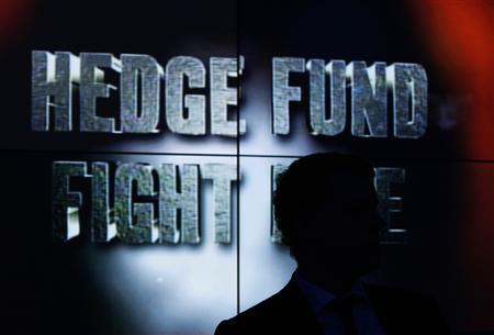 A man sits in front of a monitor displaying the title 'Hedge Fund Fight Nite' during the charity event in Hong Kong in an October 30, 2008 file photo. REUTERS/Bobby Yip (CHINA)