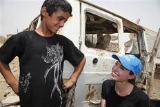 <p>Un niño desplazado sonríe junto a la embajadora de buena voluntad de Naciones Unidas Angelina Jolie en Bagdad, 23 jul 2009. La embajadora de buena voluntad de la ONU Angelina Jolie, en su tercer viaje a Irak en dos años, pidió el jueves ayuda para un estimado de 1,6 millones de civiles de ese país que siguen desplazados de sus hogares. REUTERS/Boris Heger/UNHCR/Handou</p>