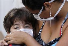 <p>Una donna e un bimbo con la mascherina protettiva a Rio de Janeiro, in Brasile, per prevenire la diffusione della nuova influienza H1N1. La foto è di ieri. REUTERS/Sergio Moraes</p>