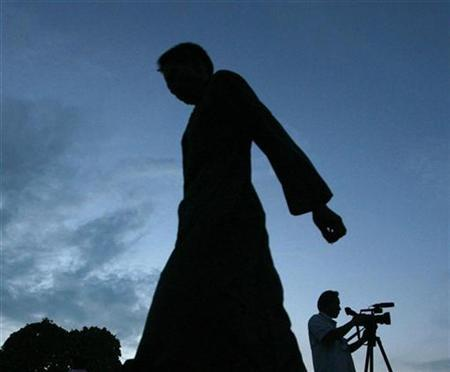 A anti-government protestor walks past a camera man filming outside the Government House in Bangkok on September 10, 2008. REUTERS/Kerek Wongsa