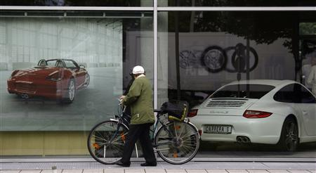 A unidentified pedestrian walks past a shopping window of a Porsche car dealer in Munich in this June 22, 2009 file photo. REUTERS/Michael Dalder/Files