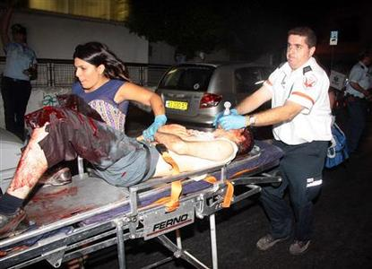 An Israeli paramedic rushes a wounded man to an ambulance after a shooting incident in a basement club in central Tel Aviv August 1, 2009. REUTERS/Amir Meiri