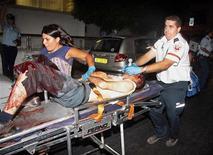 <p>Un paramedico soccorre un ferito dopo la sparatoria a Tel Aviv. REUTERS/Amir Meiri</p>
