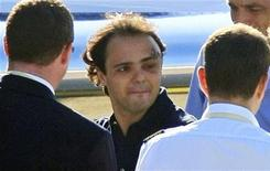 """<p>Гонщик команды """"Феррари"""" Фелипе Масса (в центре) в аэропорту Будапешта 3 августа 2009 года. Гонщик команды """"Феррари"""" Фелипе Масса, получивший серьезную травму головы во время квалификации на """"Гран-при Венгрии"""", в понедельник выписался из больницы Будапешта и на частном самолете вылетел на родину в Бразилию. REUTERS/Viktor Veres</p>"""