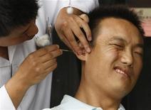 <p>Реакция мужчины на чистку ушей в чайном доме в Чэнду, Китай 10 сентября 2007 года. Клиент, которого выгнали из салона по очистке ушей, был арестован в Токио по подозрению в нападении на работницу заведения и убийстве ее бабушки, сообщает газета Yomiuri. REUTERS/Jason Lee</p>
