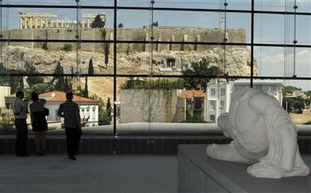 Visitors look at the temple of the Parthenon from inside the new Acropolis museum in Athens June 21, 2009. REUTERS/Yiorgos Karahalis