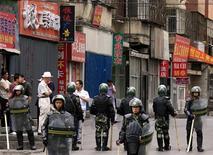 <p>Китайские полицейские охраняют одну из улиц Урумчи 13 июля 2009 года. Китайская полиция задержала 718 человек по подозрению в участии в этнических беспорядках в Синьцзян- Уйгурском автономном районе в июле, в ходе которых погибли 197 человек, сообщило во вторник государственное информационное агентство Синьхуа со ссылкой на главу Бюро общественной безопасности столицы района - города Урумчи - Чэня Чжуанвэя. REUTERS/David Gray</p>