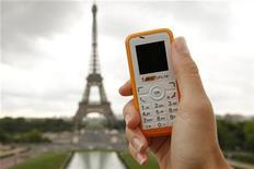<p>A woman holds a BIC phone in front of the Eiffel Tower in Paris August 7, 2008. REUTERS/Benoit Tessier</p>