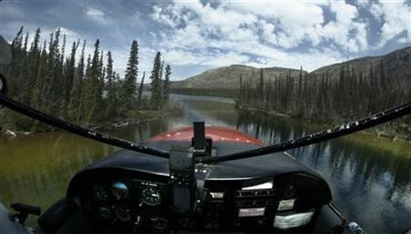 A bush plane flies just above the water through trees of the boreal forest north of Whitehorse, Yukon in this file photo taken June 21, 2007. REUTERS/Andy Clark/File