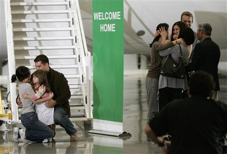 Freed U.S. journalist Euna Lee (L) is embraced by her husband Michael Saldate (2nd L) and daughter Hana Saldate after arriving with Laura Ling (3rd R) who is embraced by sister Lisa Ling and mother Mary in Burbank, California August 5, 2009. Ling, 32, and Lee, 36, American journalists freed by North Korea from months of detention, returned to U.S. soil early on Wednesday accompanied by Clinton, who secured their release in a meeting with the hermit state's leader Kim Jong-il. REUTERS/Danny Moloshok
