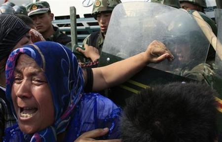 A woman pushes at Chinese soldiers wearing riot gear as a crowd of angry locals confront security forces on a street in the city of Urumqi in China's Xinjiang Autonomous Region July 7, 2009. REUTERS/David Gray