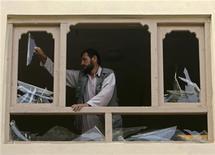 """<p>Мужчина вытаскивает разбившееся стекло из окна недалеко от места атаки в Кабуле 4 августа 2009 года. Боевики исламистского движения """"Талибан"""" атаковали в понедельник афганские правительственные объекты к югу от столицы страны, сообщили чиновники и местные жители. REUTERS/Omar Sobhani</p>"""