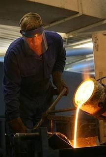 A worker casts an ingot of gold at Kolyma Refinery in the village of Khasyn, 80 km (50 miles) north of Magadan, July 19, 2009. Moscow's fragmented gold industry has struggled to access vast reserves in inhospitable parts of the Far East, a region first mined in the 1930s by prisoners of Soviet leader Josef Stalin's Gulags. Picture taken July 19, 2009. REUTERS/Robin Paxton