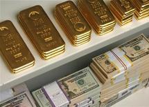 <p>Золотые слитки и пачки долларов США в сейфе банка в Вене 21 июля 2009 года. Таджикистан обратился через ООН к мировому сообществу с просьбой выделить $7 миллионов для ликвидации последствий весенних ливневых дождей, сообщил в среду офис Программы развития ООН. REUTERS/Heinz-Peter Bader</p>