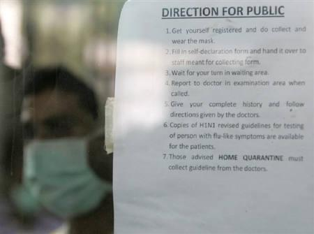 A man wearing a mask stands behind a notice at a hospital in New Delhi August 11, 2009. REUTERS/Fayaz Kabli