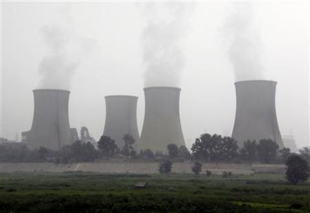 A small house stands in front of a coal-burning power station located on the outskirts of Beijing August 5, 2009. REUTERS/David Gray