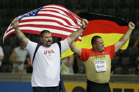 Christian Cantwell of the U.S. and Ralf Bartels of Germany (R) hold their national flags as they celebrate after the men's shot put final during the world athletics championships at the Olympic stadium in Berlin August 15, 2009. REUTERS/Michael Dalder
