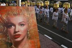 <p>People walk past a portrait of Marilyn Monroe as they carry offerings during a procession of Pelebon or The Royal Cremation Ceremony in Ubud, on the Indonesian island of Bali, July 13, 2008. REUTERS/Beawiharta</p>