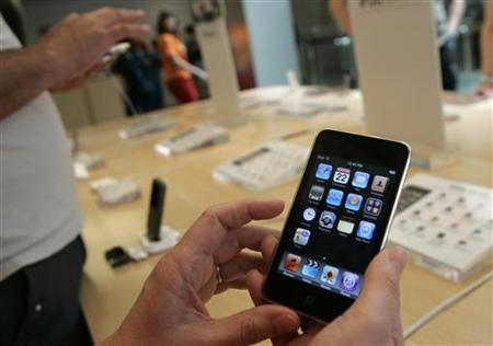 Customers look over an Apple iTouch at the company's retail store in San Francisco, California April 22, 2009. REUTERS/Robert Galbraith